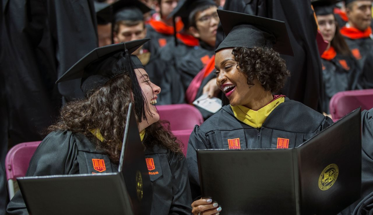 2 master's degree students laughing together after receiving their diplomas at commencement