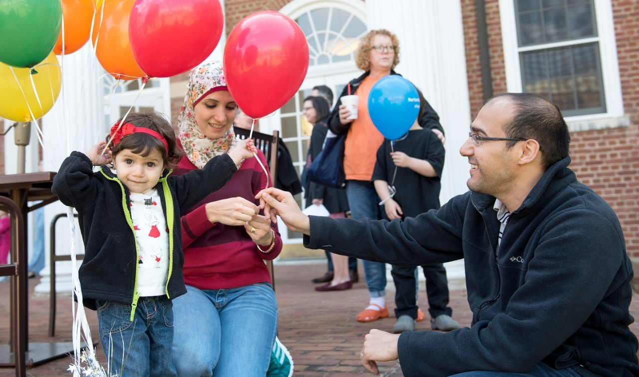 Parents giving their daughter a balloon at the Graduate Life Center