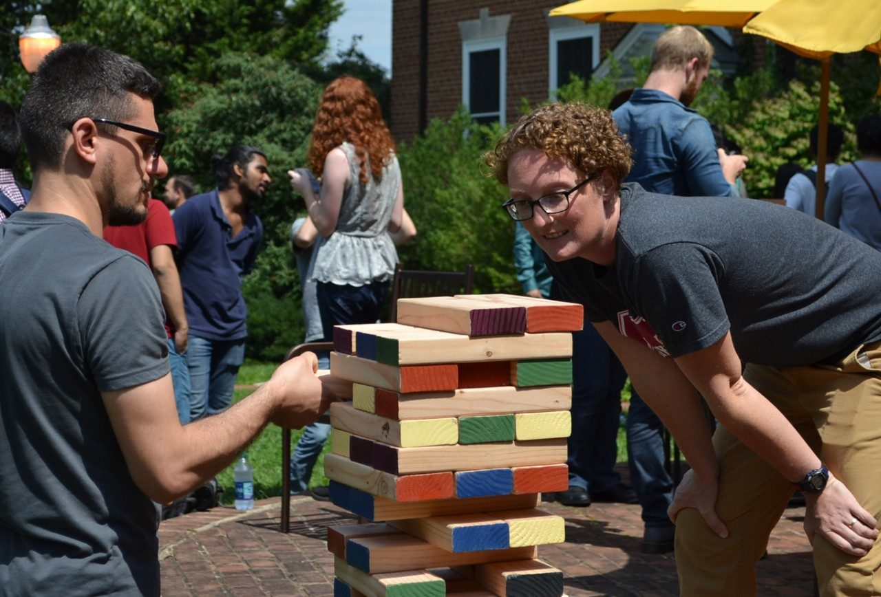 Graduate students playing with giant Jenga blocks on the Graduate Life Center patio during an event