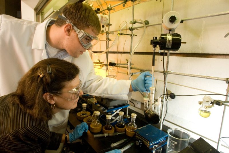 A male graduate student and a female graduate student wearing protective glasses working with pipettes in a lab