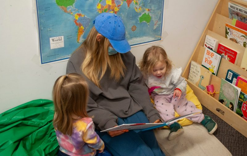 A father giving his toddler daughter a red balloon. The little girl is holding the strings of other balloons, and there are other children and their parents in the background
